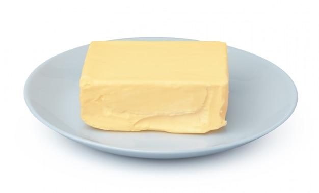 白い壁に分離された白いプレート上のバター