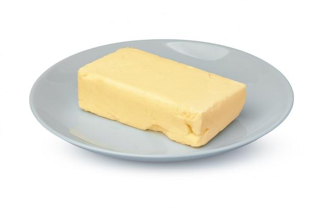 白で隔離される白いプレート上のバター