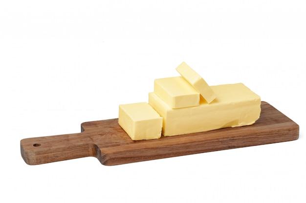 白い背景で隔離された木の板にバターします。