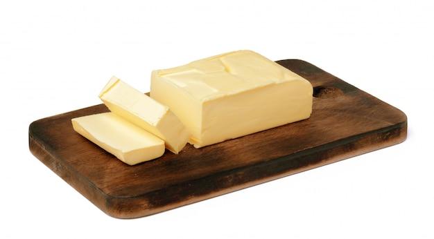 白い壁に分離された木の板にバター