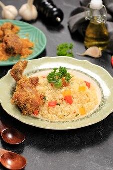 Рис со сливочным маслом и жареной курицей, наси горенг ментега с аям горенг серунденг. подается на керамической тарелке, черный фон