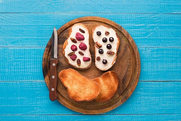 신선한 라즈베리, 건포도, 건포도를 얹은 건강한 통밀 빵에 버터 샌드위치. 평면도. 정물. 텍스트를 위한 공간입니다.