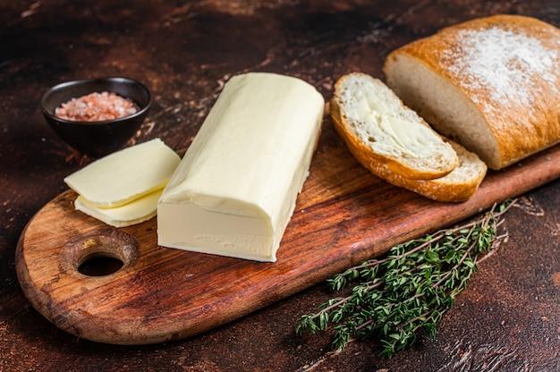 버터 스프레드와 식료품은 나무 도마에 토스트합니다. 어두운 테이블. 평면도.