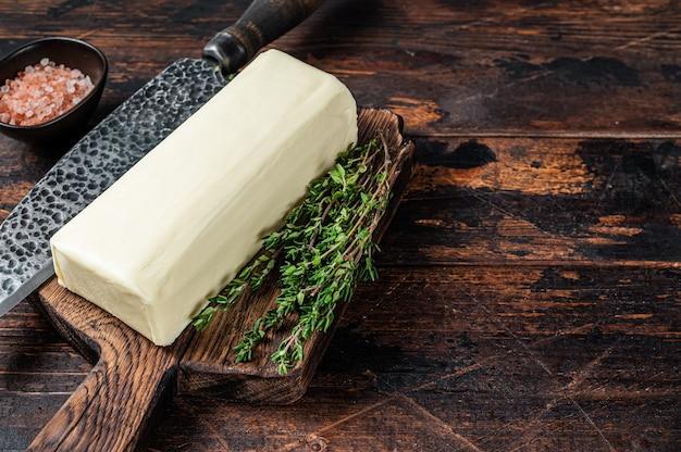 Блок сливочного масла выкладывают на деревянную доску. темный деревянный фон. вид сверху. скопируйте пространство.