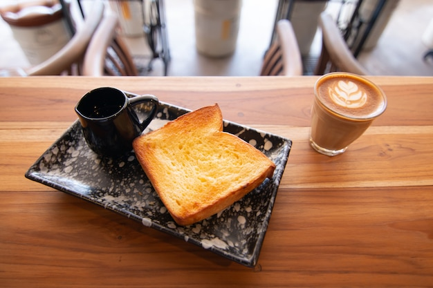 Butter and sugar toast with honey on wooden desk in coffee shop