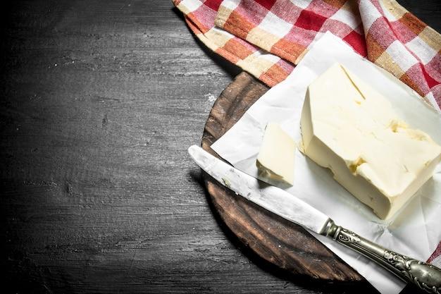 黒い黒板に乗ったナイフでバターを塗る。