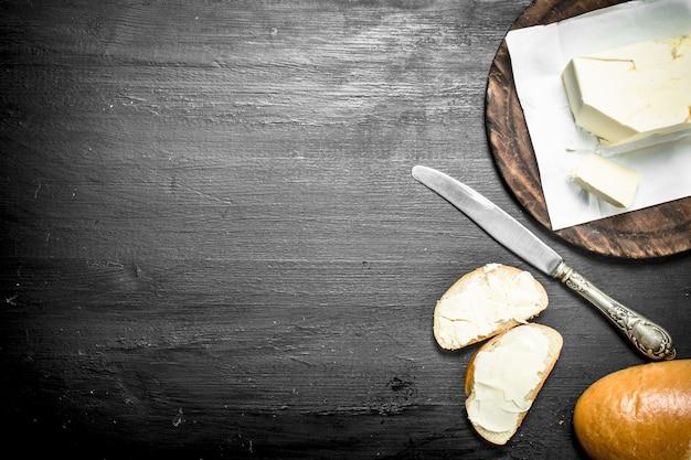 ボード上でナイフでバターを塗る。黒い黒板に。