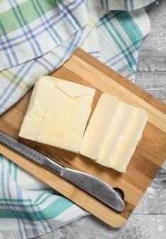 Сливочное масло с салфеткой. на деревенском столе.