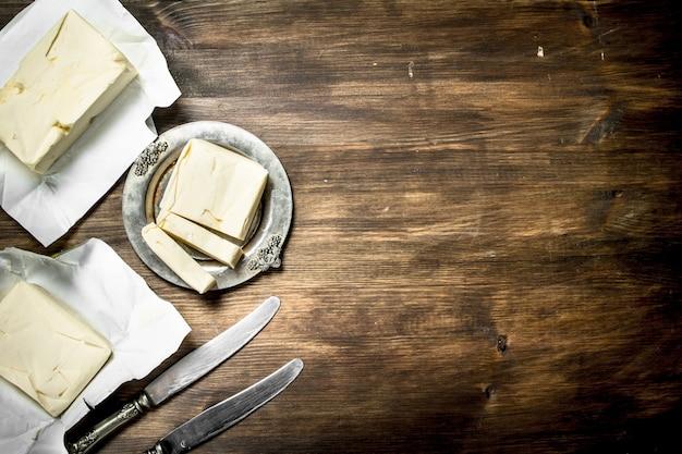 木製のテーブルにナイフでバター。