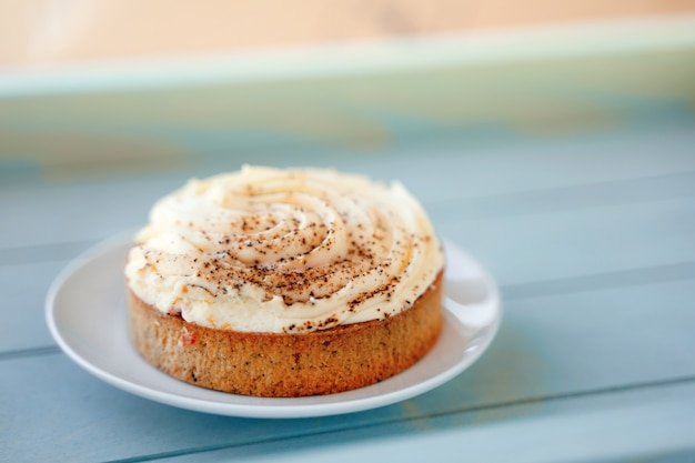 Buttercream and cinnamon cake on a blue tray