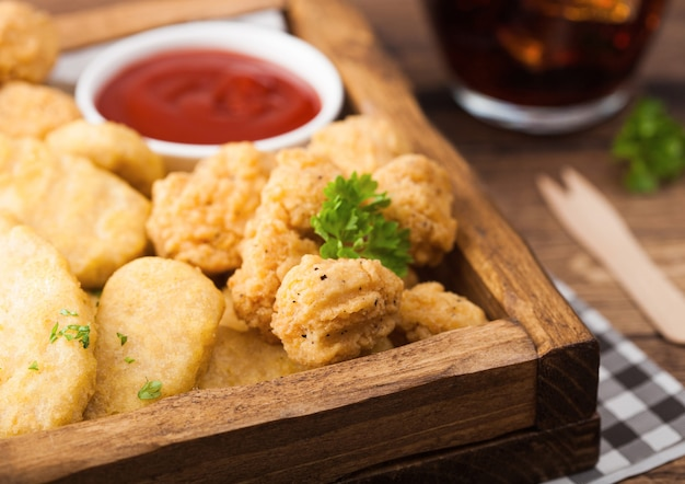 Buttered chicken nuggets and popcorn bites in vintage wooden box with ketchup and glass of cola on wood background.