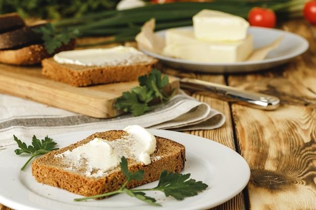 木製のテーブルの背景にライ麦パンのバタースライス