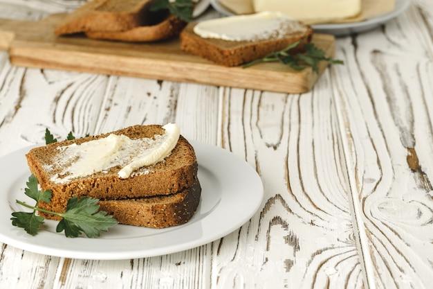 木製のテーブルにライ麦パンのバタースライス