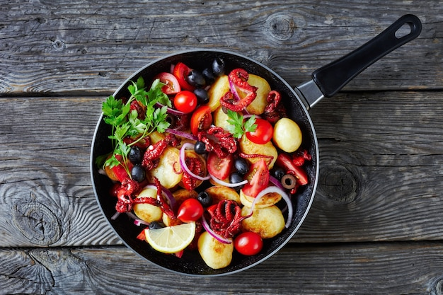 ベビータコまたはモスカルディーニ、トマト、ブラックオリーブ、赤玉ねぎのスライスを添えたバターを塗った若いポテトサラダ、木製テーブルのフライパンで提供、上面図、クローズアップ