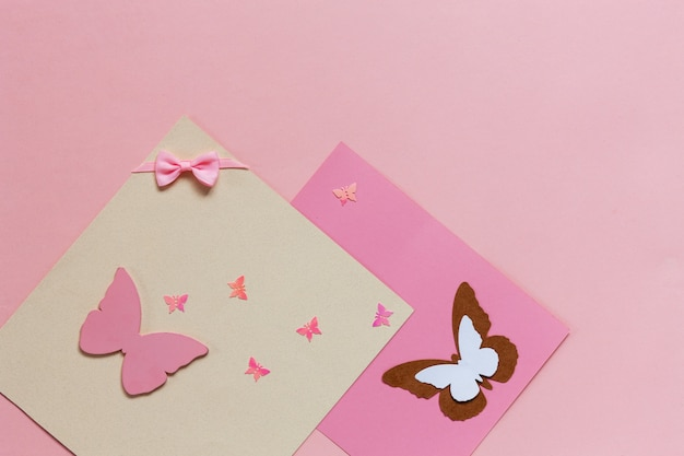 Butterfliy figyrines on the pink paper background