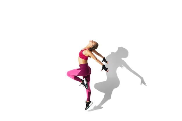 Butterfly. beautiful young female athlete practicing on white  wall, portrait with shadows. sportive fit model in motion and action. body building, healthy lifestyle, style concept.
