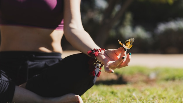 Butterfly on meditating woman