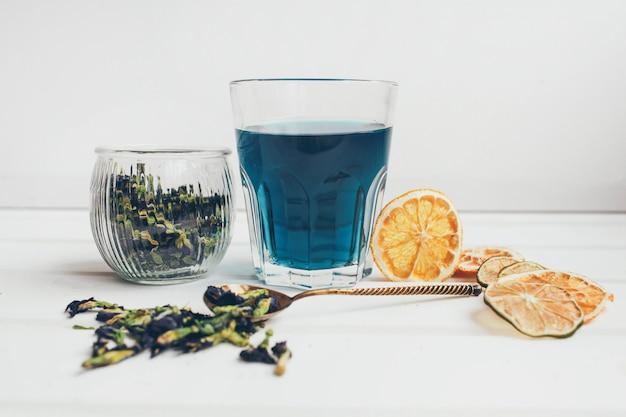 バタフライピーフラワーブルーティー。暗いテーブルで飲むデトックス。健康的なハーブドリンク。ライム入りブルーハーブティーあんちゃん