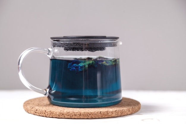 Butterfly pea flower blue tea. healthy detox herbal drink. butterfly pea tea in transparent teapot on white wooden table