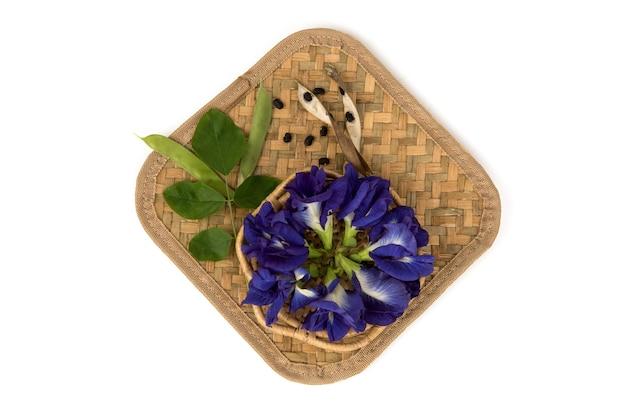 蝶エンドウ豆の花と緑の葉が白い表面に分離されました。上面図、フラットレイ。