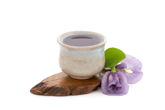 蝶エンドウ豆の花と白い背景で隔離のお茶。上面図、フラットレイ。