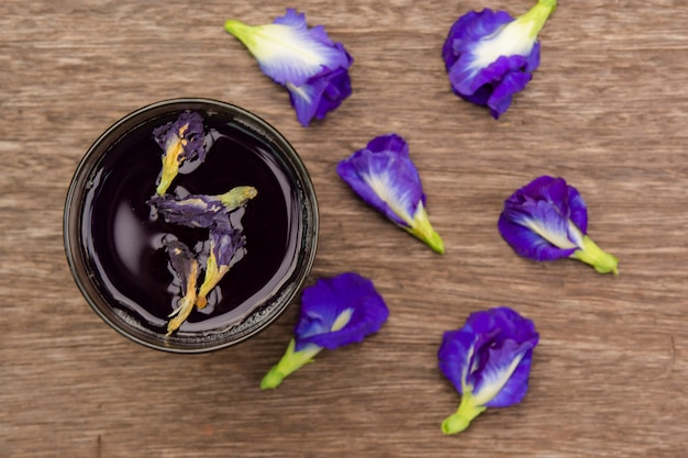 Butterfly pea juice and butterfly pea flower on wood