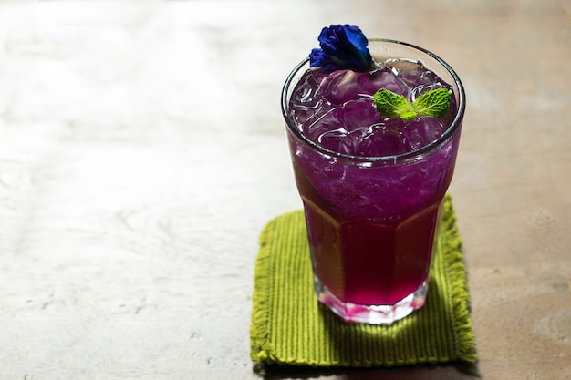 Butterfly pea juice with lemon in cold glass, thai herb drink for health.