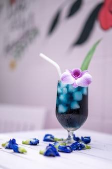 紫色の蘭とパンダンの葉で屋外フィールド装飾のセメント壁の前にパステルピンクの木製テーブルの蝶エンドウ豆。