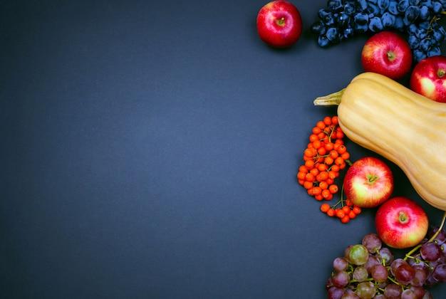 Мускатный орех, яблоки, виноград и ягоды рябины на черном