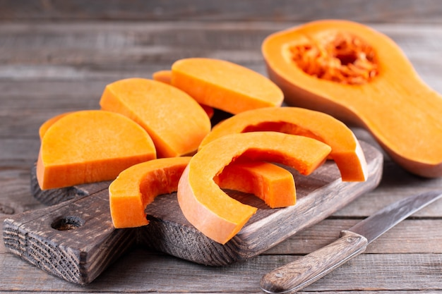 Butternut squash meal preparation on wooden kitchen table. cooking food for traditional thanksgiving dinner. making autumn pumpkin soup.