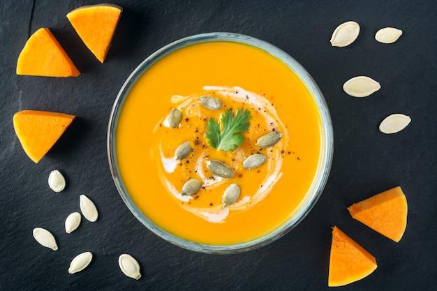 ボウルにバタースカッシュのスープ。バタースカッシュのスライスとスレートボード上の種。健康的なベジタリアン料理。ハロウィーン、感謝祭のディナー。スペースをコピーします。