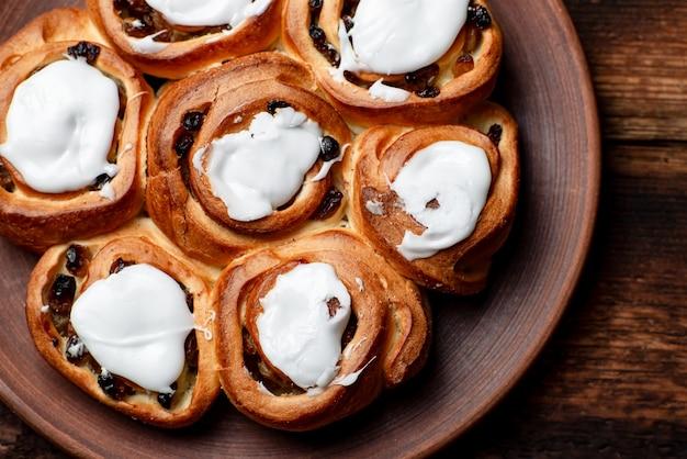 Масляные сладкие булочки с изюмом на коричневой глиняной тарелке. покрыт белым сахарным сиропом.