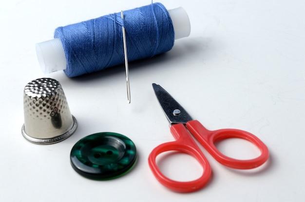ボタン、針付き糸ボビン、指ぬき、小さなはさみ、ボタン