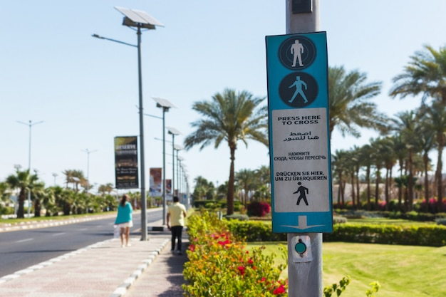 Button for calling the pedestrian crossing with the up arrow. click here to cross it written in four languages english, arabic, russian and german