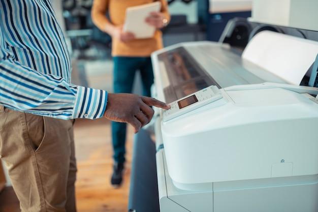 プリンタのボタン。ポスターの印刷中にプリンターのボタンを押す浅黒い肌の労働者のクローズアップ