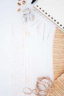 ボタン;指ぬき針;スパイラルメモ帳。ニット生地と木製のテーブルの文字列