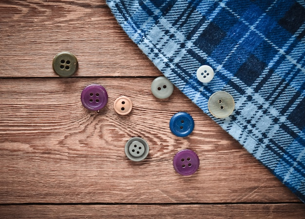 Buttons, cloth shirt on a wooden table. top view, copy space.