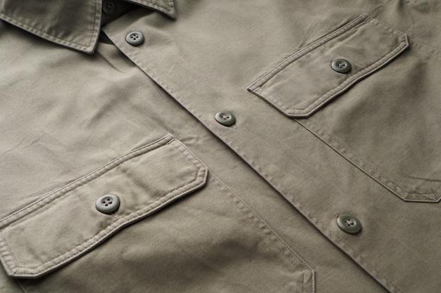 ボタン、ポケット、襟、縫い目、シャツの要素。緑の天然綿で作られた既製のシャツを縫いました。ファッションデザイン要素、ファッションの背景。