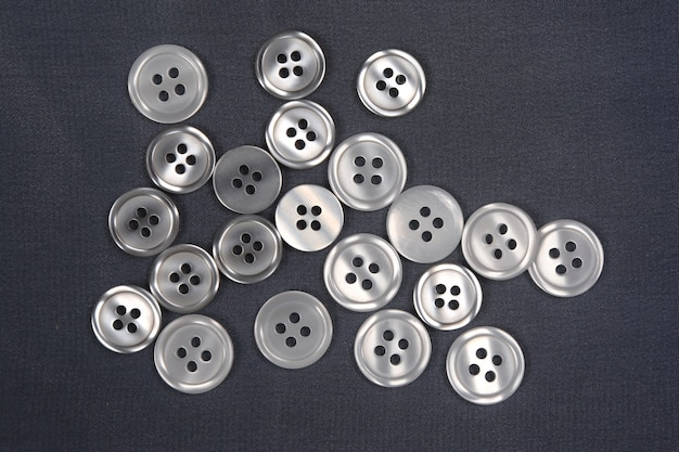 Buttons scattered on a dark cloth