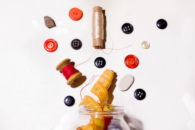 Buttons and threads of different colors spill out of the can on a white space. concept of mending old things and sewing