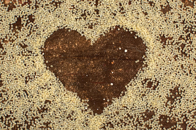 Abbottona la forma di cuore circostante gialla su un pavimento marrone rustico di legno