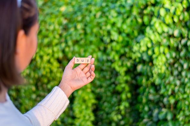 «купить» алфавит в женской руке перед домом. - купить дом и концепцию недвижимости.