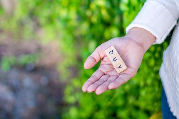 «купить» алфавит в руке женщины.