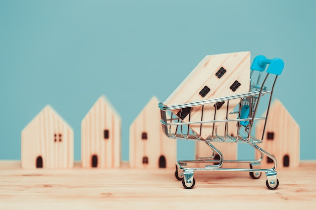 Buy home shopping sale wood house with cart or shop new house promotion accommodation mortgage and loans concept.