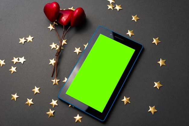 Buy online gift for your valentine, red hearts and green screen on tablet