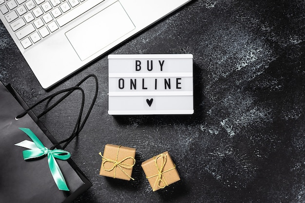 Buy online text on the lightbox, laptop, gift boxes and bags on black rustic background