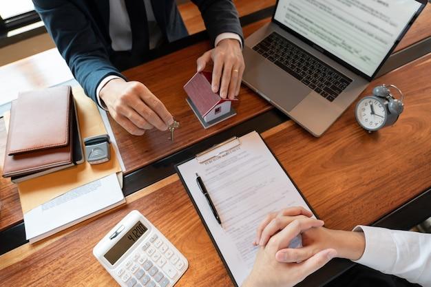 Концепция покупки или продажи недвижимости, торговый представитель предлагает договор купли-продажи дома на покупку дома или квартиры