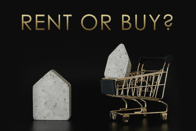 Buy or rent, choice. house model in mini shopping cart on the black background. buy a house. concept for property ladder, mortgage and real estate investment.