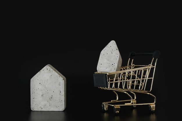 Buy or rent choice house model in mini shopping cart on the black background buy a house