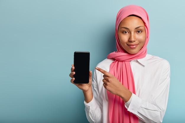 このデバイスを購入してください!ピンクのベールで満足している暗い肌の女性、スマートフォンを指す